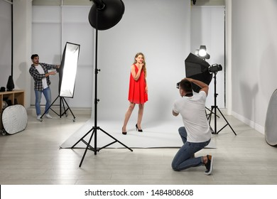 Professional photographer with assistant taking picture of young woman in modern studio