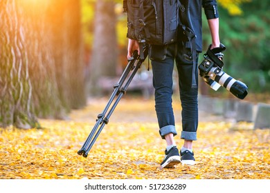professional photographer with camera and tripod in autumn.