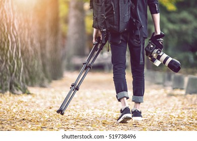 professional photographer with camera and tripod in autumn. Vintage tone.