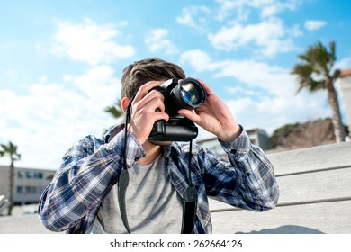 Professional photographer in casual clothes taking pictures with camera on the bench in the tropical city