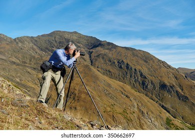 Professional photographer making landscape photos by digital mirror camera and tripod at rock mountainon