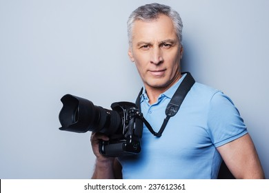 Professional photographer. Portrait of confident mature man in T-shirt holding camera while standing against grey background