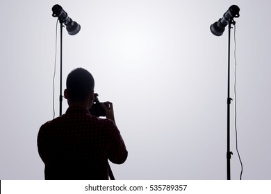 Professional photographer. Portrait of confident young man in shirt holding hand on camera while standing against grey background
