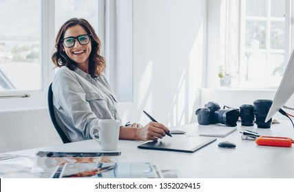 Professional photographer sitting at her office desk looking away and smiling. Woman in office with digital graphic tablet and drawing pen.