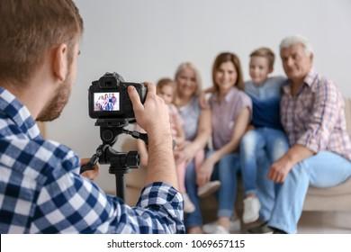 Professional photographer taking photo of family on sofa in studio