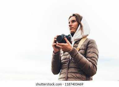 professional photographer tourist traveler standing on on a white background holding in hands digital photo camera, hiker view from front taking photography, girl enjoy relax holiday hobby concept
