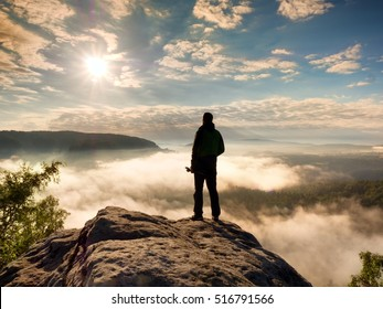 Professional photographer with tripod in hands on cliff and thinking. Dreamy fogy landscape, blue misty sunrise in a beautiful valley below