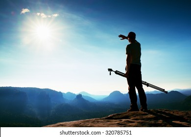 Professional photographer with tripod on cliff and thinking. Dreamy fogy landscape, blue misty sunrise in a beautiful valley below