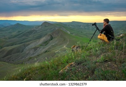 Professional photographer using a tripod, taking a photo of a mountain landscape at sunset