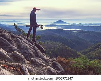 Professioneller Fotograf sieht Frühlingsofas-orangefarbenen, unangenehmen Sonnenaufgang statt Fotos. Hiker mit Spiegelkamera auf Felsspitze.