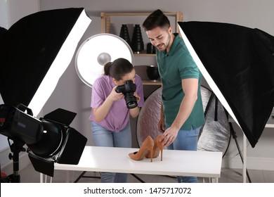 Professional photographers shooting stylish shoes in studio