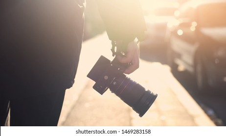 Professional photojournalist holding camera, walking on street, paparazzi spying