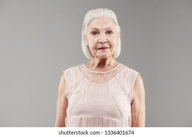 Professional photoshoot. Short-haired old woman wearing light silk blouse while posing in professional photo studio