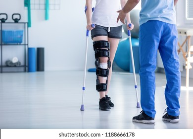Professional physiotherapist supporting patient with orthopedic problem