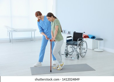 Professional physiotherapist working with female patient in rehabilitation center