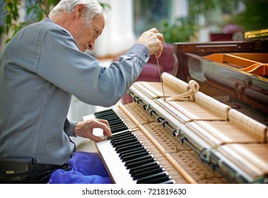 Professional piano technician repairing hammer mechanism using shank. Determined repairman trying to tune and restore vintage musical instrument keyboard.