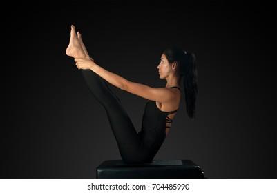 Professional pilates instructor performing double leg rocker pose