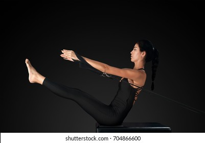 Professional pilates reformer instructor performing teaser pose