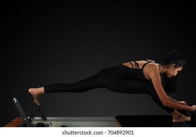 Professional pilates reformer instructor performing russian split pose
