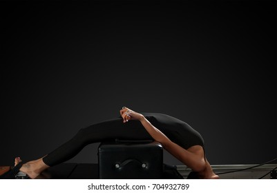 Professional pilates reformer instructor performing pilates moves
