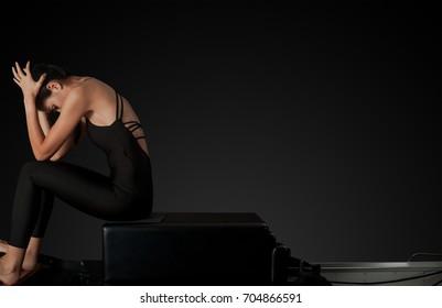 Professional pilates reformer instructor resting after workout