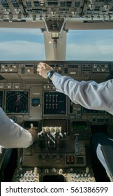 professional pilots fly and control airplane viewed from modern glass cockpit with many instrument panels