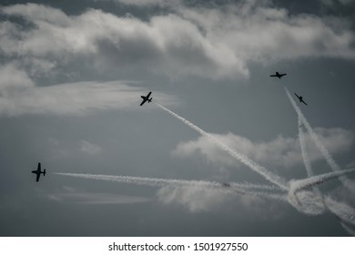 Professional pilots flying fast jets in attack formation during the air show.