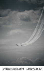 Professional pilots flying the fast jets during air show while executing dangerous maneuvers in the sky and leaving traces of smoke