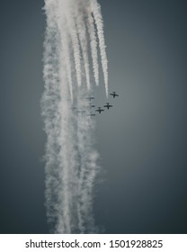 Professional pilots flying jets at the air show while executing dangerous maneuvers and leaving white traces of smoke on the blue sky