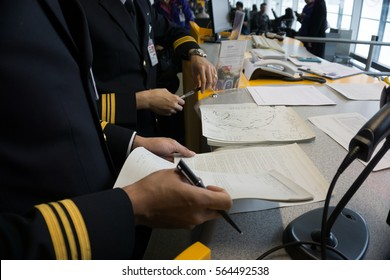 professional pilots reading and prepare their flight documents  at boarding gate before flight