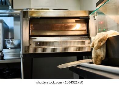 Professional pizzeria kitchen stove appliance: oven, gloves and shovel. Metallic clean stainless. pizzeria interior