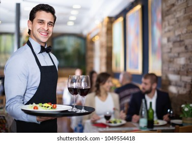 Professional pleasant waiter holding serving tray for restaurant guests