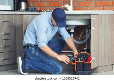 Professional plumber fixing kitchen sink