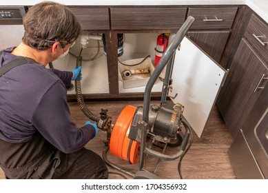 Professional plumber using an auger to clear a kitchen sink drain