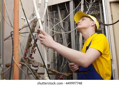 Professional plumber working on central heating boiler