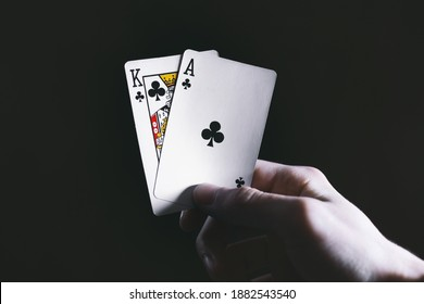 Professional Poker Player Holding Two Playing Cards, King And Ace Of Clubs On Black Background. Entertainment, Casino, Playing Cards, Tournament Concept. Soft Focus. Rome, Italy - December 26, 2020
