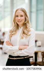 Professional portrait head shot of a Caucaasian White expatriate working in Singapore, Asia. She is middle-aged in her 30's, attractive, blond and beautiful in a crisp white shirt in an office.