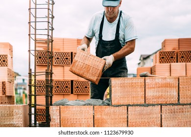 professional, portrait of industrial worker building walls with ceramic bricks