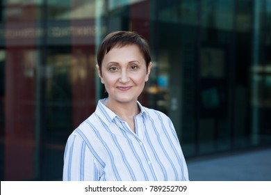Professional portrait of a middle aged business woman looking at the camera and smiling. Head shot of an older 40 50 years old businesswoman.