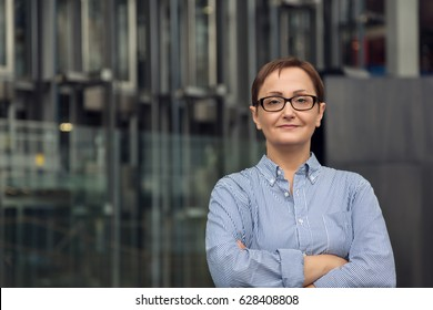 Professional portrait of middle - aged older woman in her forties - fifties,  wearing glasses and shirt. Headshot of a factory business unit manager. Blurred industrial background.