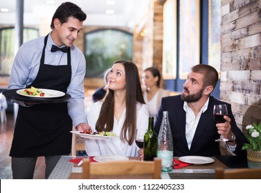 professional positive waiter man serving company of positive guests at restaurant