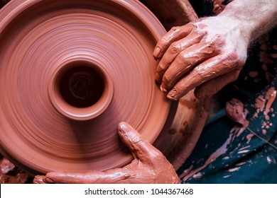 Professional potter making bowl in pottery workshop, studio.