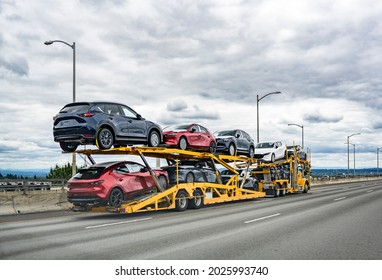 Professional powerful yellow big rig industrial car hauler semi truck with two level modular hydraulic semi trailer transporting cars moving on the wide multiline highway road with stormy sky