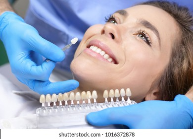 In a professional practice, a dentist checks the level of teeth whitening the patient's teeth with a dentist's color. Concept of: dentists, healthcare, perfection, white.