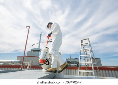 professional in protective uniform, mask, gloves in the roof for cleaning