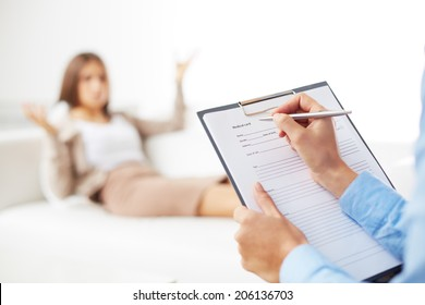 Professional psychiatrist consulting her patient and making notes in application form