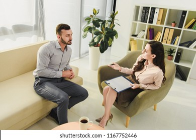 professional psychiatrist and male patient having consultation in office