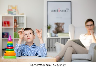 Professional psychologist observing an autistic boy in her office