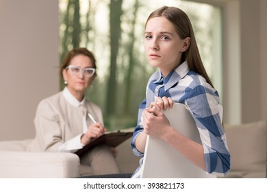 Professional psychologist treating teenage girl of depression. Young worried girl looking for help