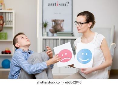 Professional psychologist working with autistic boy in her office
